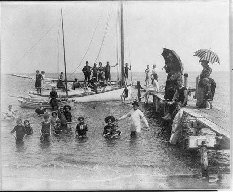 Hommes, femmes et enfants en maillot de bain à quai, sur des bateaux à voile et dans l'eau; Frances Benjamin Johnston est assise sur le bord d'un petit bateau à moteur