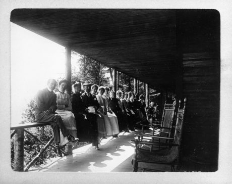 E. Alice Austen, Large group sitting on a porch railing - 1899